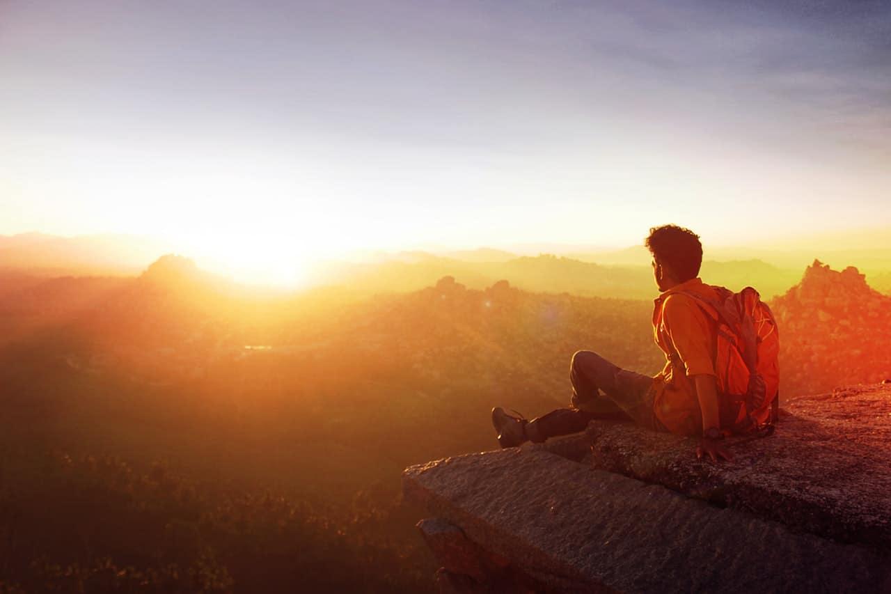 man-sitting-on-edge-facing-sunrise