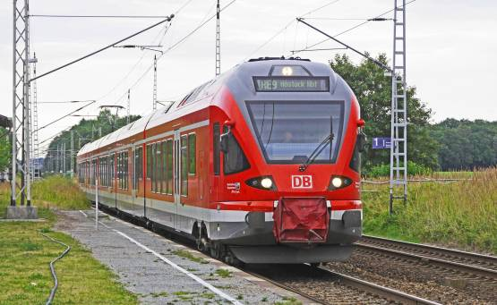 red-train-on-tracks-with-green-grass-beside-under-bright-sky