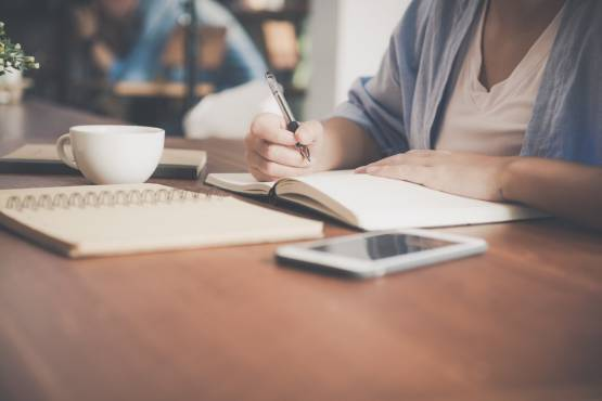 woman-writing-on-a-notebook-beside-teacup-and-tablet